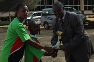 Prof Chris Wanjala of University of Nairobi hands prizes to winners during a Kenya Book Week event in Nairobi.